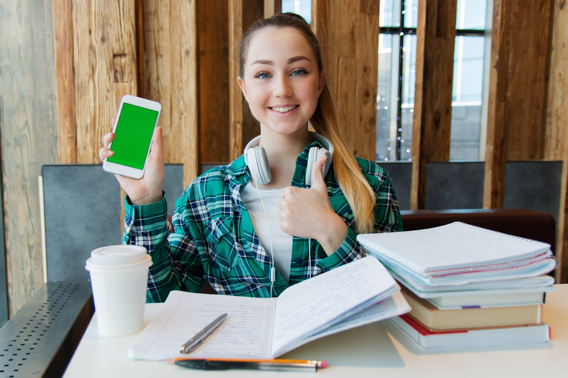 smiling woman holding white android smartphone while sitting front of table